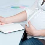schwangere frau schreibt etwas in ihren kalender